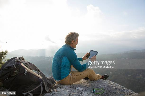 Hiker relaxes with digital tablet on stone ledge
