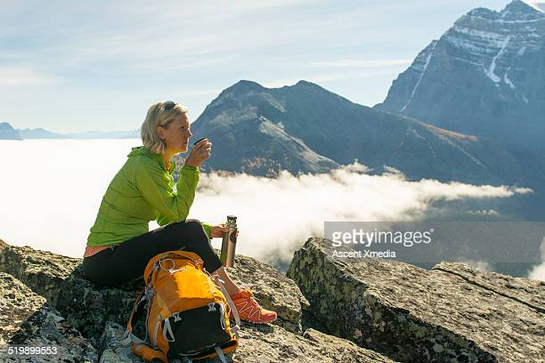 Hiker relaxes with thermos of hot beverage, mtns