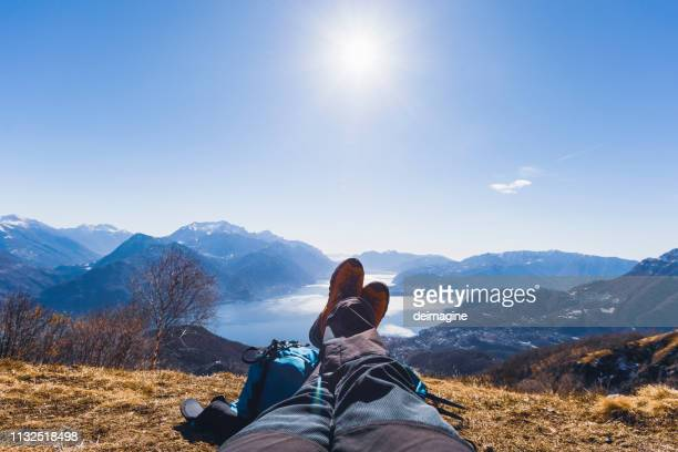 hiker relaxing over hill, lake in background - patagonia foto e immagini stock