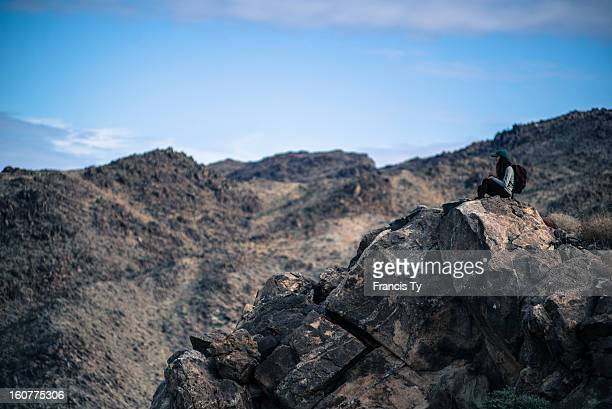 Hiker resting on a rock overlook at Joshua Tree National Park California