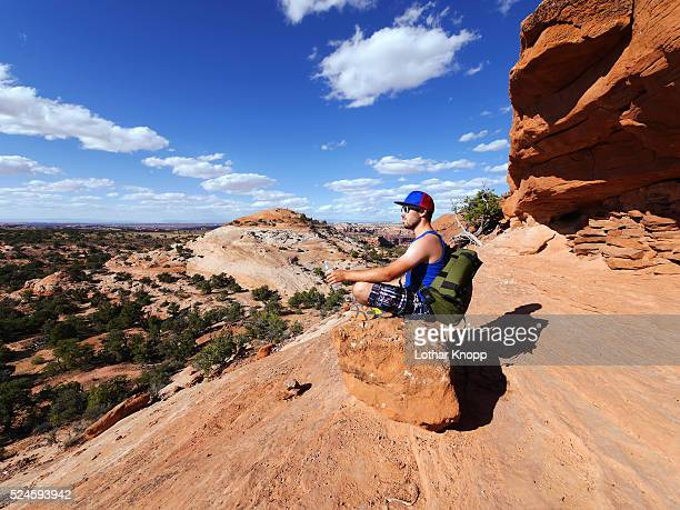 hiker resting on aztec butte, canyonlands national park, usa - islands in the sky stock pictures, royalty-free photos & images
