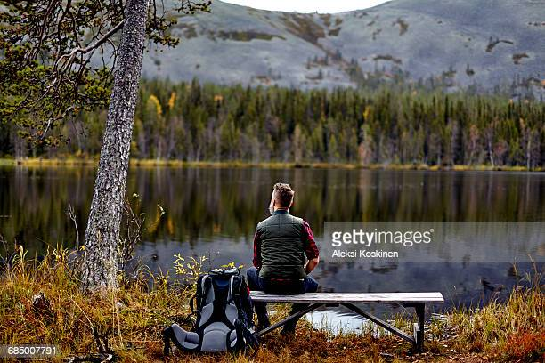 hiker resting on bench, looking out at lake, kesankijarvi, lapland, finland - finlandia fotografías e imágenes de stock