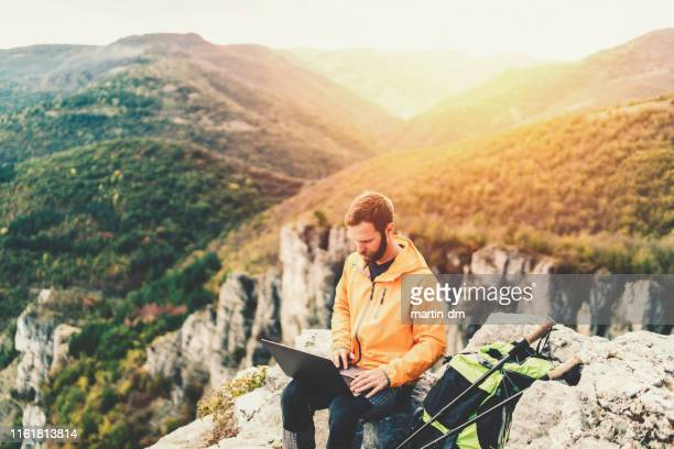 hiker resting on the mountain peak - nomadic people stock pictures, royalty-free photos & images