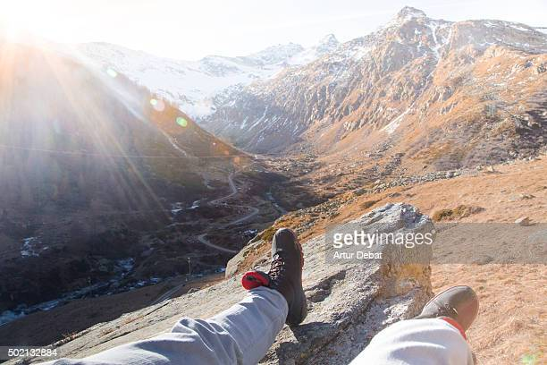 Hiker resting on the rock with the Gran Paradiso national park views from personal point of view.