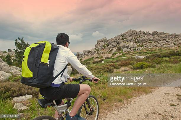 hiker riding bicycle on field against cloudy sky - tempio pausania stock pictures, royalty-free photos & images