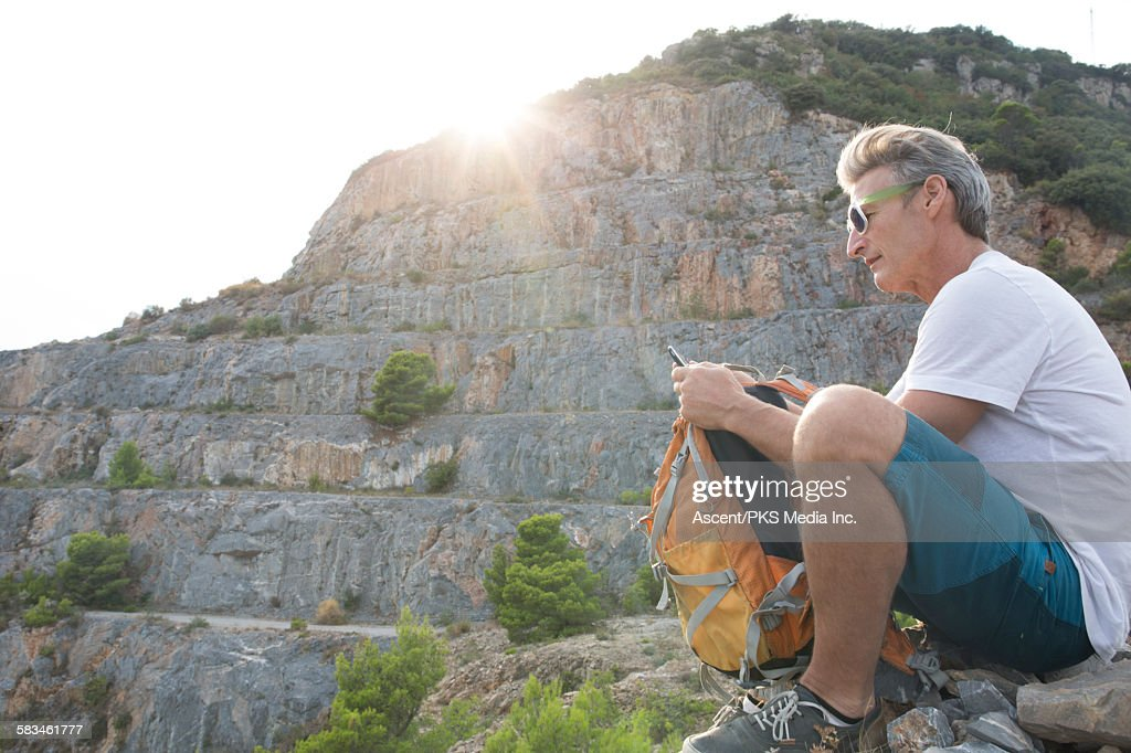 Hiker sends text from rest spot below old quarry : Stock Photo