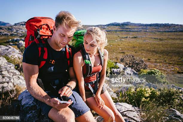 Hiker showing girl friend map on smartphone during outdoor activ