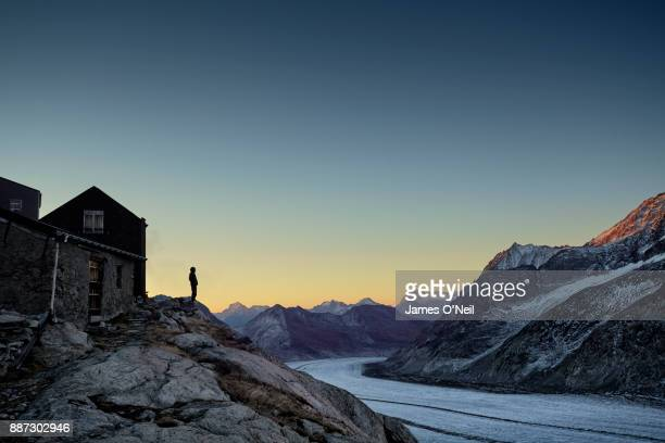 Hiker silhouette watching sunrise over mountain range and glacier, Aletsch Glacier, Switzerland