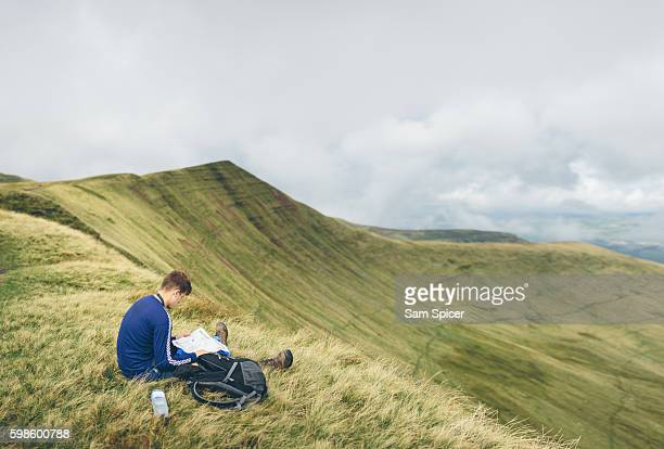Hiker sitting looking at map whilst orienteering in mountain landscape