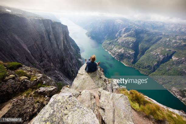 hiker sitting on kjeragnasen over lyseford in norway - high up stock pictures, royalty-free photos & images