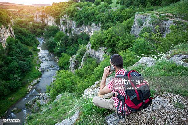 Hiker sitting on mountain peak and using phone
