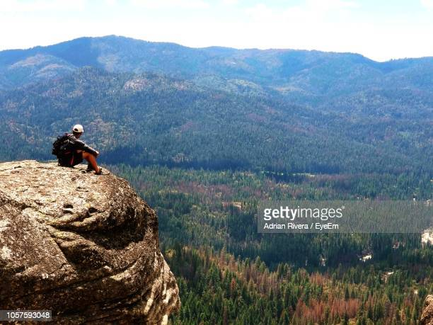 hiker sitting on mountain while looking at view - only mid adult men stock pictures, royalty-free photos & images