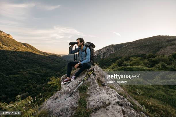 hiker sitting on rock looking through binoculars - looking through an object stock pictures, royalty-free photos & images
