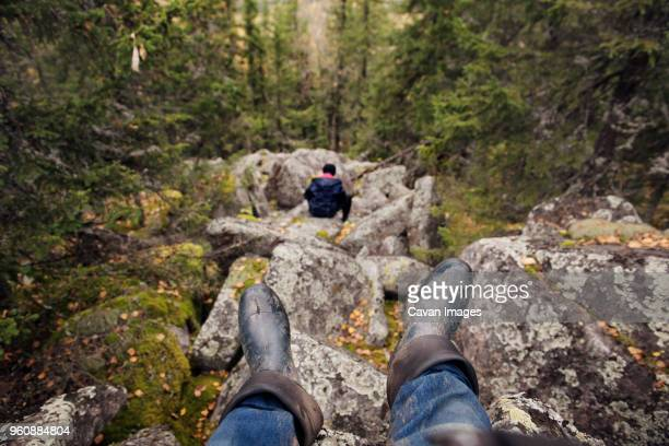 Hiker sitting on rocks in forest