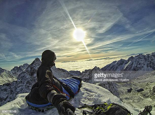 Hiker Sitting On Snow Covered Mountain During Sunset