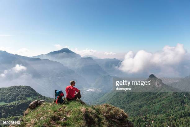 hiker sitting on top of mountain - bergamo stock pictures, royalty-free photos & images
