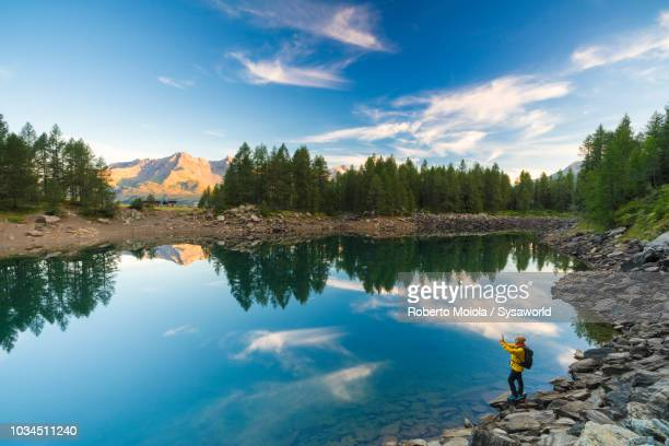 hiker snaps pictures at lago azzurro, madesimo - mirror lake stock pictures, royalty-free photos & images