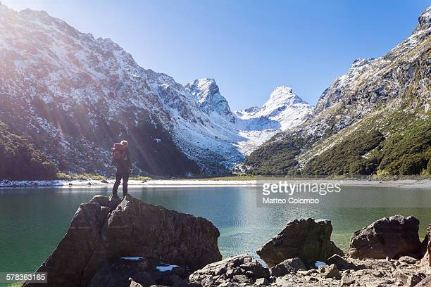 hiker standind at lake mackenzie, routeburn track - southland new zealand stock pictures, royalty-free photos & images