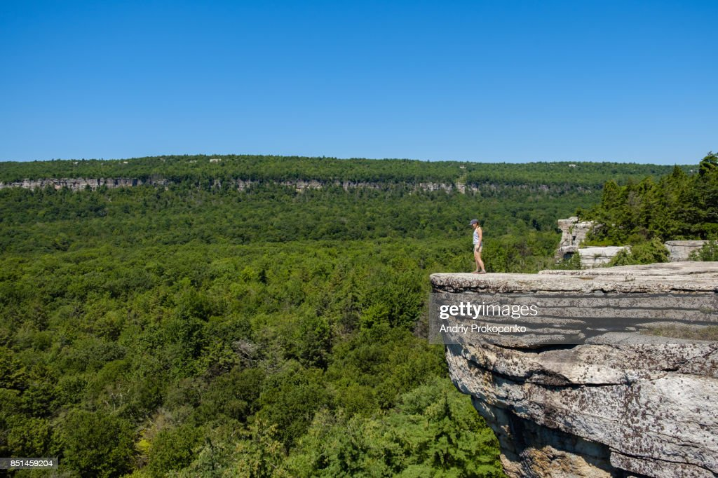 Hiker standing at the edge of the cliff : Stock Photo
