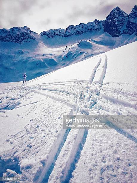 Hiker Standing By Cross Shape Snow Tracks By Rocky Mountains Against Sky