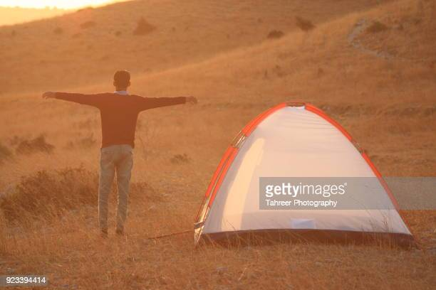 A hiker standing by the camp with open arms