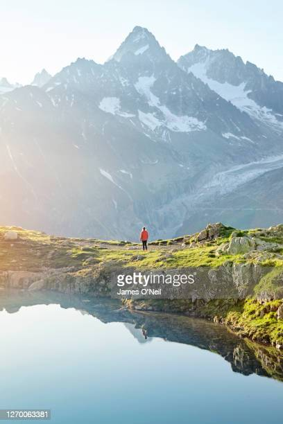 hiker standing in front of mountains at lake blanc, chamonix - front view photos et images de collection