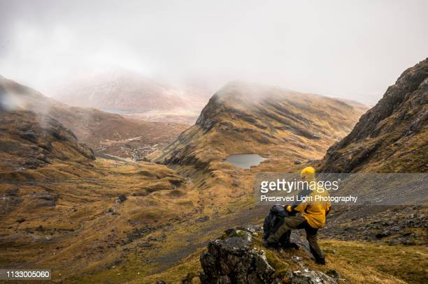 hiker standing on a rocky outcropping of bla bheinn mountain, braving the wet and windy elements of the scottish highlands in spring, isle of skye, scotland - light natural phenomenon ストックフォトと画像