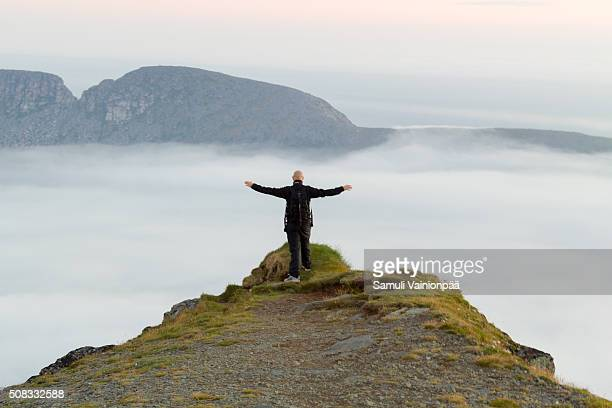 Hiker standing on cliff, arms outstretched