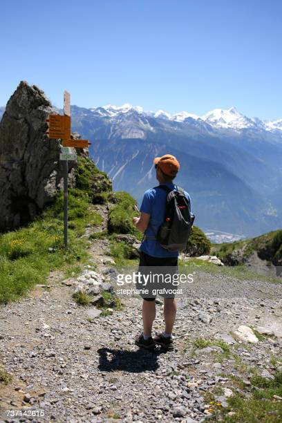 Hiker standing on footpath in mountains, Switzerland