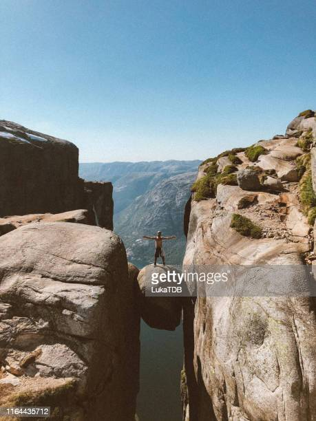 hiker standing on kjeragbolten in norway - high up stock pictures, royalty-free photos & images