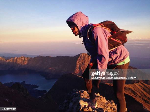 Hiker Standing On Rock At Mount Rinjani Against Sky During Sunset
