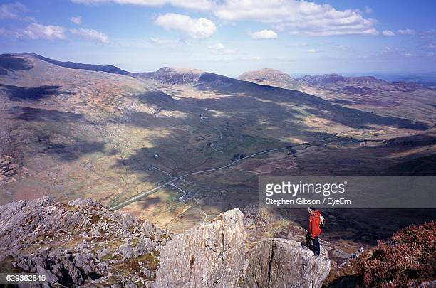 Hiker Standing On Rock Formation At Snowdonia National Park Against Sky