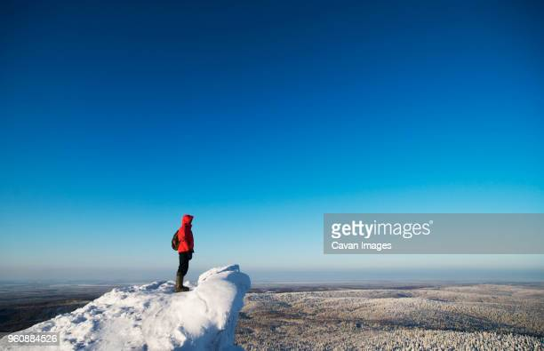 hiker standing on snow covered mountain against clear blue sky - yekaterinburg foto e immagini stock