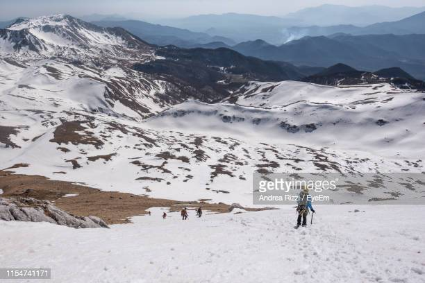 hiker standing on snowcapped mountain - andrea rizzi stock pictures, royalty-free photos & images