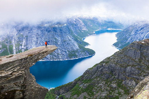 Hiker standing on Trolltunga with panoramic view of lake, Norway 804595788