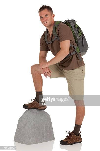 Wanderer stehend mit seinem einem Fuß auf einem boulder