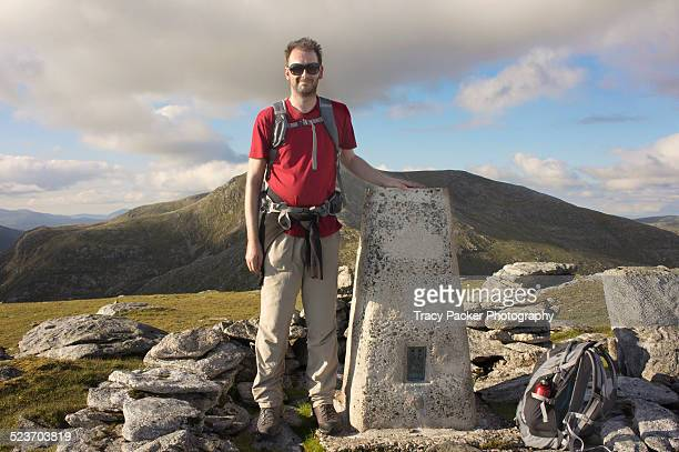 A hiker stands at a trig-point on a Scottish Hill