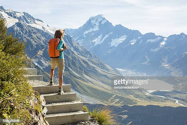 hiker stands on a mountain top and admires view - new zealand stock pictures, royalty-free photos & images