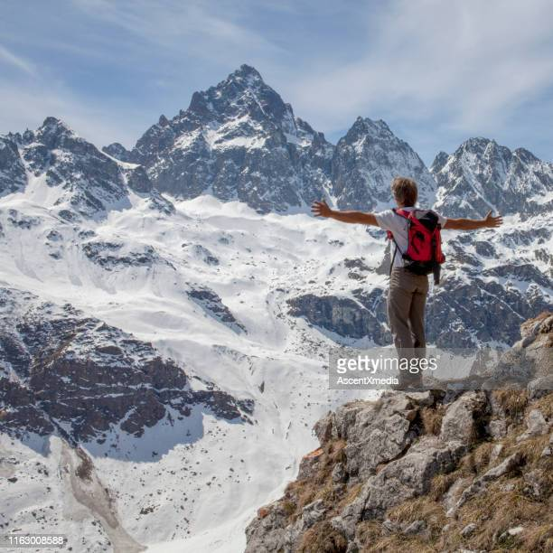 hiker stands on cliff top with arms out - early retirement stock pictures, royalty-free photos & images