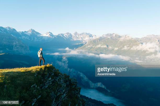 hiker stands on mountain meadow crest - switzerland stock pictures, royalty-free photos & images