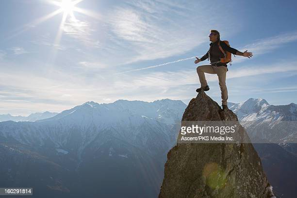 hiker stands on pinnacle summit, arms outstretched - bergpiek stockfoto's en -beelden