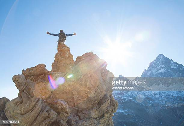Hiker stands on pinnacle summit, spreads arms wide