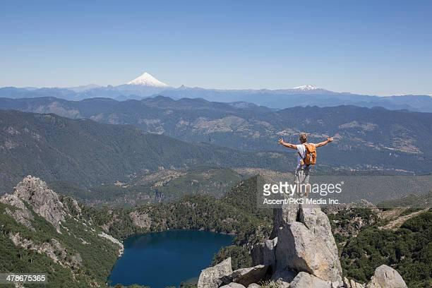 hiker stands on rock above valley, arms outstretch - pucon fotografías e imágenes de stock