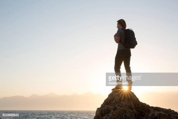 Hiker stands on rock promontory, looks to sea