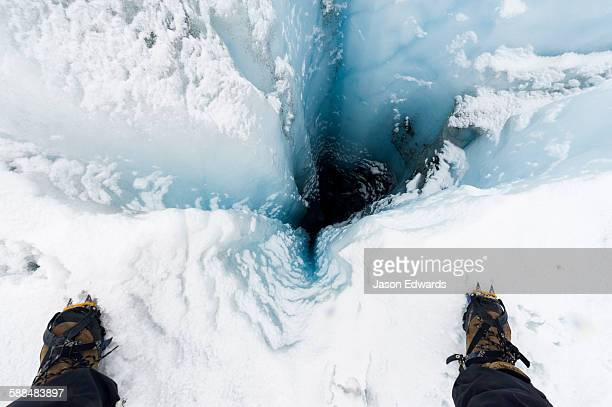A hiker stands over a moulin, a narrow, tubular chute or crevasse through which water enters a glacier from the surface.