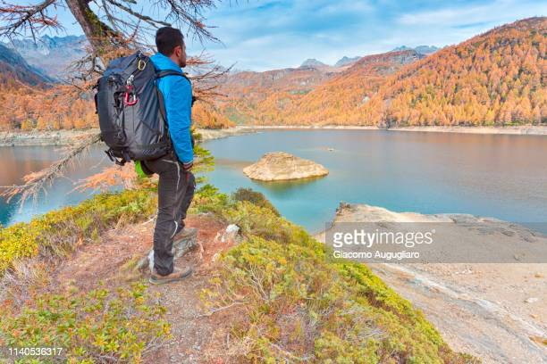 hiker staring at lake devero in autumn, alpe vein alpe devero valley, baceno, verbano cusio ossola province, piedmont, italy - province of verbano cusio ossola stock pictures, royalty-free photos & images