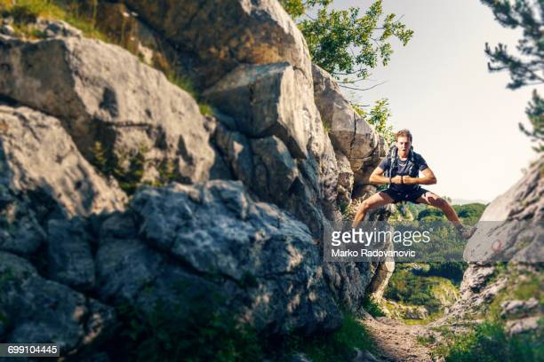 Hiker staying above the trail with legs wide spread between two rocky slopes
