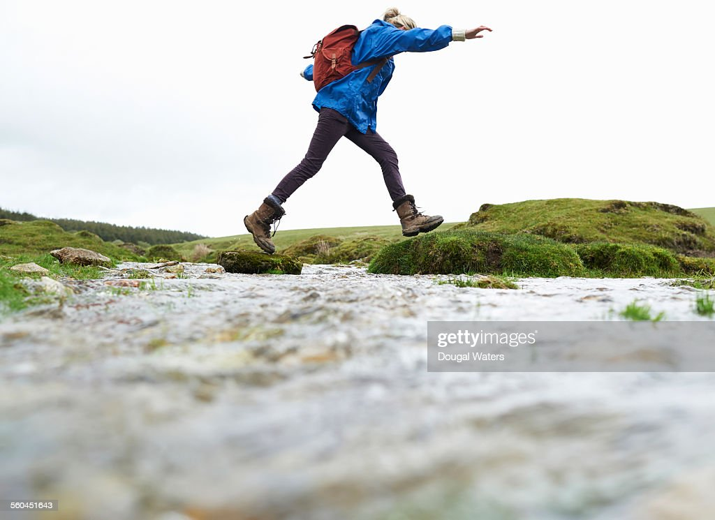 Hiker stepping across stream in countryside : Stockfoto