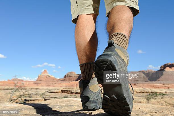 Hiker Stepping Forward Through Rocky Terrain