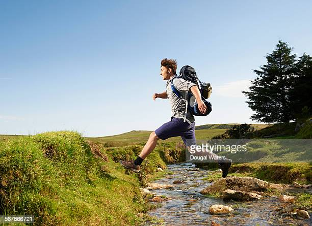 hiker stepping over stream in countryside. - dougal waters stock pictures, royalty-free photos & images